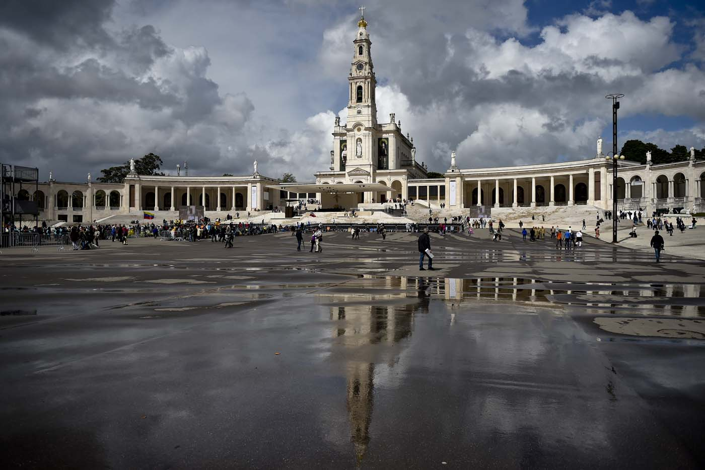 """Nossa Senhora do Rosario de Fatima"" basilica reflects on the wet ground at Fatima shrine, central Portugal, on May 11, 2017.  Two of the three child shepherds who reported apparitions of the Virgin Mary in Fatima, Portugal, one century ago, will be declared saints on May 13, 2017 by Pope Francis. The canonisation of Jacinta and Francisco Marto will take place during the Argentinian pontiff's visit to a Catholic shrine visited by millions of pilgrims every year. / AFP PHOTO / PATRICIA DE MELO MOREIRA"