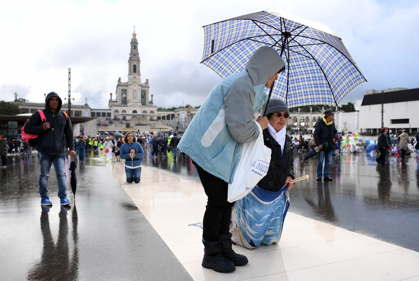 A woman covers with an umbrella another woman walking on her knees at Fatima Sanctuary, central Portugal, on May 12, 2017.  Two of the three child shepherds who reported apparitions of the Virgin Mary in Fatima, Portugal, one century ago, will be declared saints on May 13, 2017 by Pope Francis. The canonisation of Jacinta and Francisco Marto will take place during the Argentinian pontiff's visit to a Catholic shrine visited by millions of pilgrims every year. / AFP PHOTO / Francisco LEONG