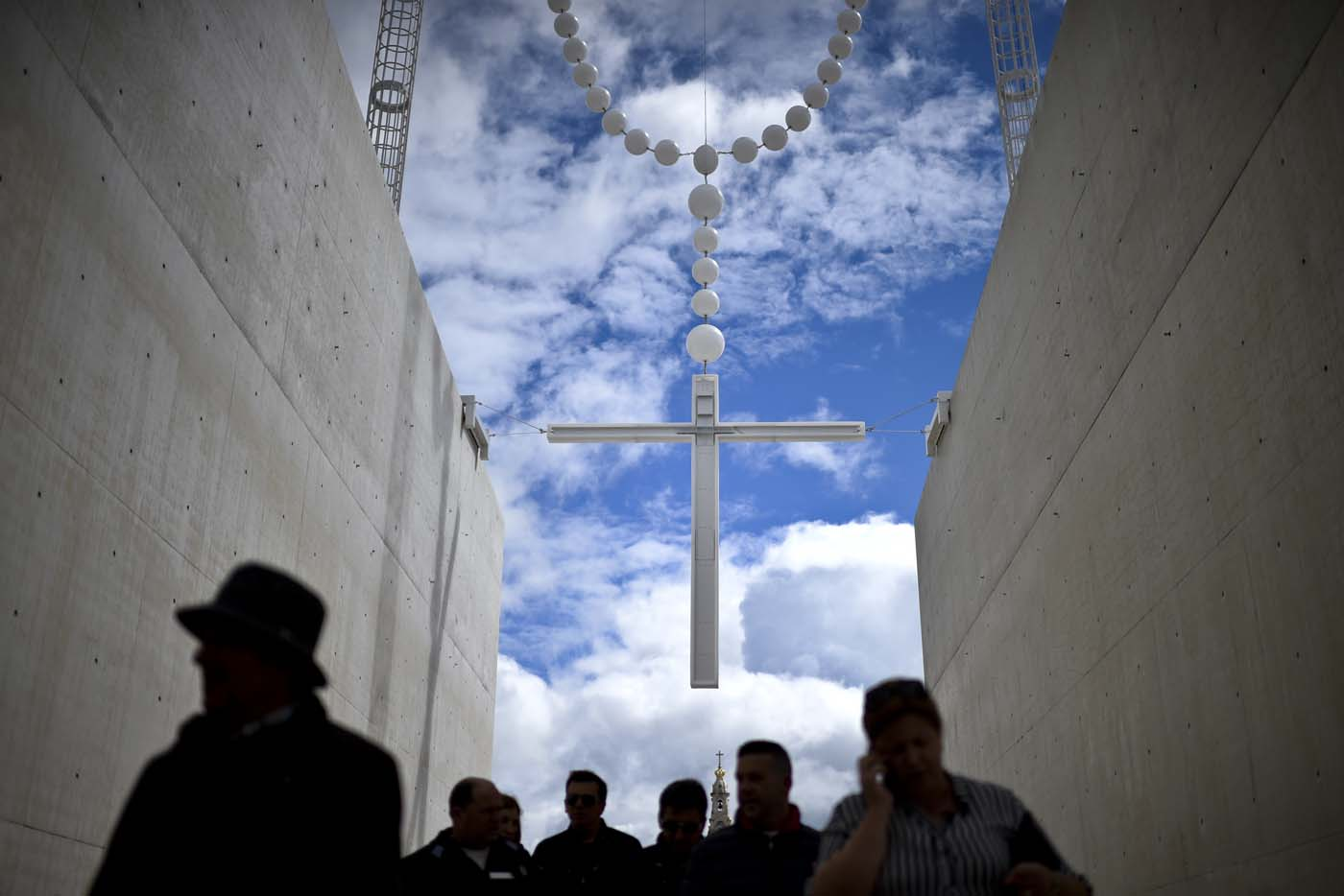 People walk under a giant rosary hanging at Fatima Sanctuary in Fatima, central Portugal, on May 12, 2017.   Two of the three child shepherds who reported apparitions of the Virgin Mary in Fatima, Portugal, one century ago, will be declared saints on May 13, 2017 by Pope Francis. The canonisation of Jacinta and Francisco Marto will take place during the Argentinian pontiff's visit to a Catholic shrine visited by millions of pilgrims every year. / AFP PHOTO / PATRICIA DE MELO MOREIRA
