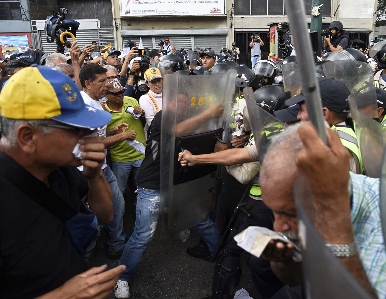 Opposition activists confront riot police during a protest against the government in Caracas on May 12, 2017. Daily clashes between demonstrators -who blame elected President Nicolas Maduro for an economic crisis that has caused food shortage- and security forces have left 38 people dead since April 1. Protesters demand early elections, accusing Maduro of repressing protesters and trying to install a dictatorship. / AFP PHOTO / JUAN BARRETO