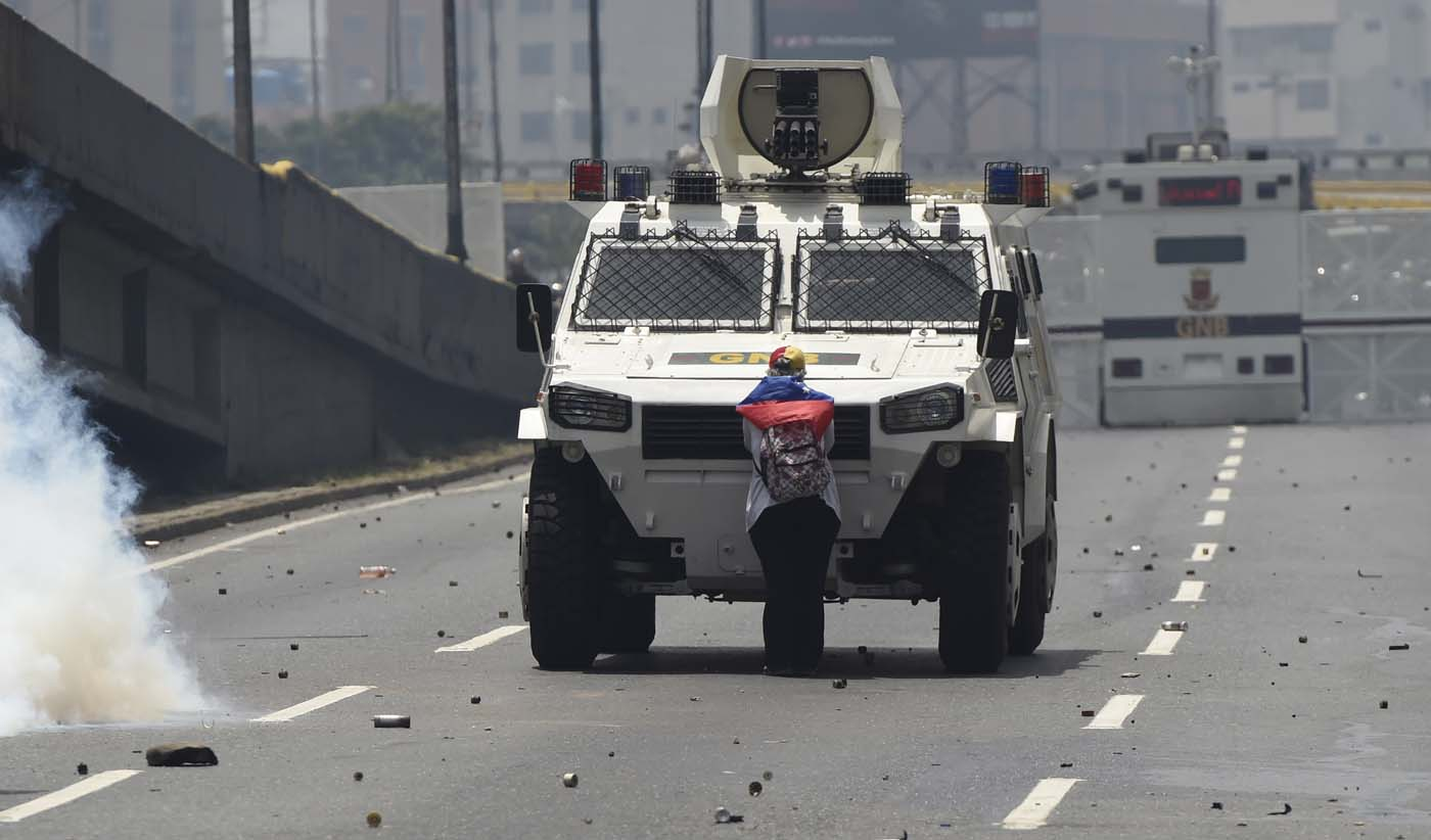 "(FILES) This file photo taken on April 19, 2017 shows a demonstrator standing in front of an armoured vehicle of the riot police during a rally against Venezuelan President Nicolas Maduro, in Caracas on April 19, 2017. ""It hurt me to see how they were firing at the kids,"" she said later, referring to the rubber bullets and tear gas used by police against protesters.  / AFP PHOTO / Juan BARRETO"