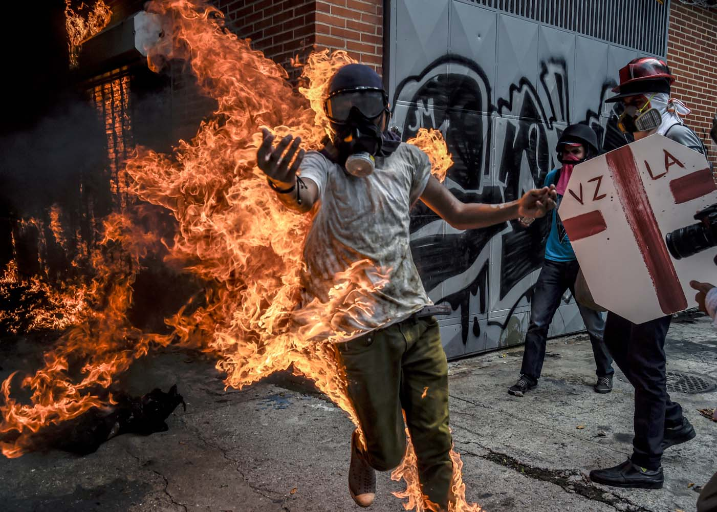 "(FILES) This file photo taken on May 03, 2017 shows a demonstrator catching fire after the gas tank of a police motorbike exploded during clashes in a protest against Venezuelan President Nicolas Maduro, in Caracas on May 3, 2017. From his hospital bed where he lay in bandages with burns on 70 percent of his body, Victor Salazar sent a video urging protesters: ""Get out into the street, not for me but for Venezuela."" / AFP PHOTO / JUAN BARRETO"