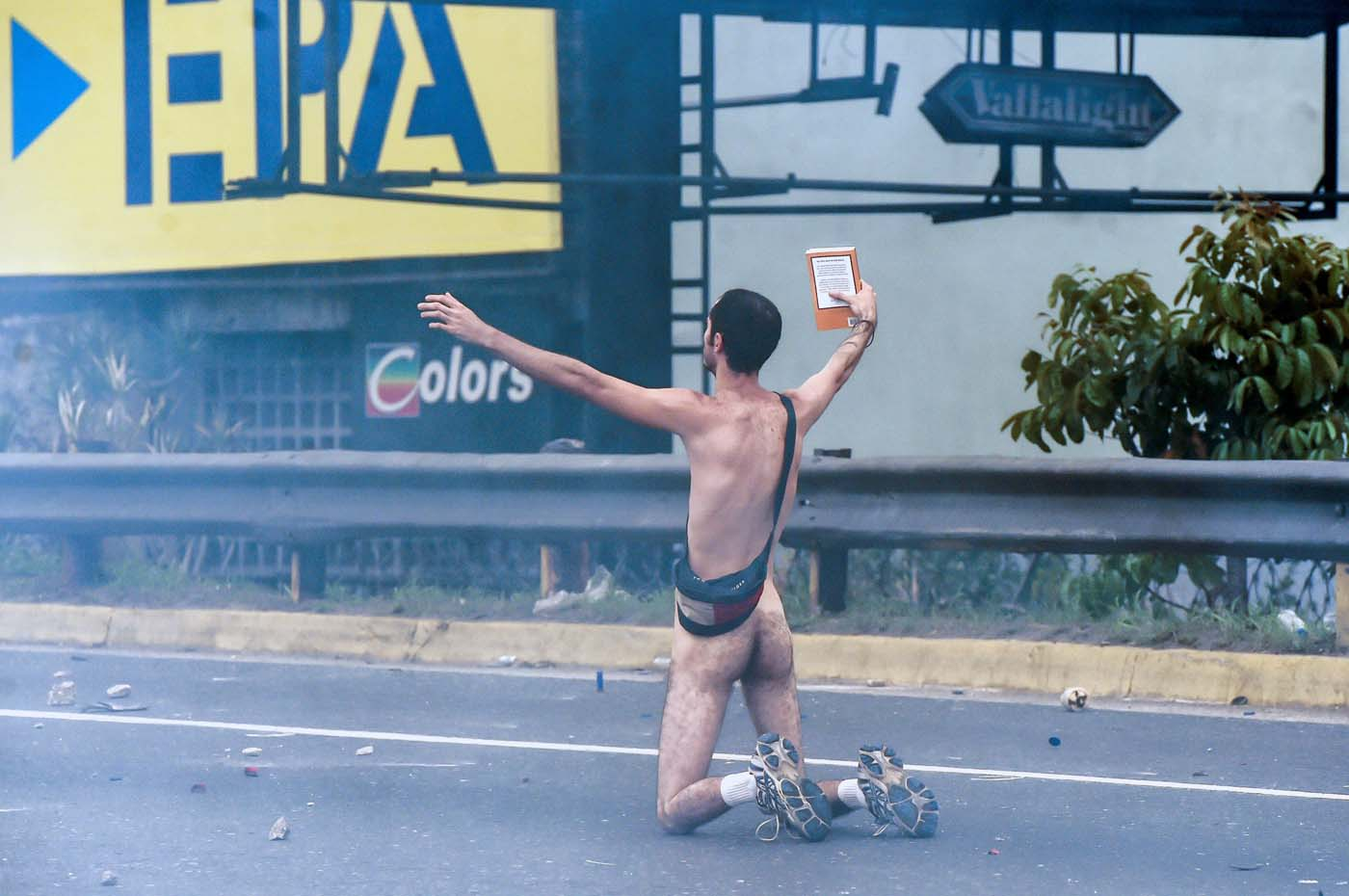 "EDITORS NOTE: Graphic content / (FILES) This file photo taken on April 20, 2017 shows a naked demonstrator taking part in a protest against Venezuelan President Nicolas Maduro, in Caracas on April 20, 2017. Wearing nothing but white sports shoes and socks, a money belt and an anguished expression, Hans Wuerich, 27, raised a bible in his skinny hand as he stood on top of a police armored car on April 20. ""I'm not some flower-power hippy,"" he told AFP later. ""But I do believe that peaceful protest does more harm to the government than violence. I stunned them."" / AFP PHOTO / JUAN BARRETO"