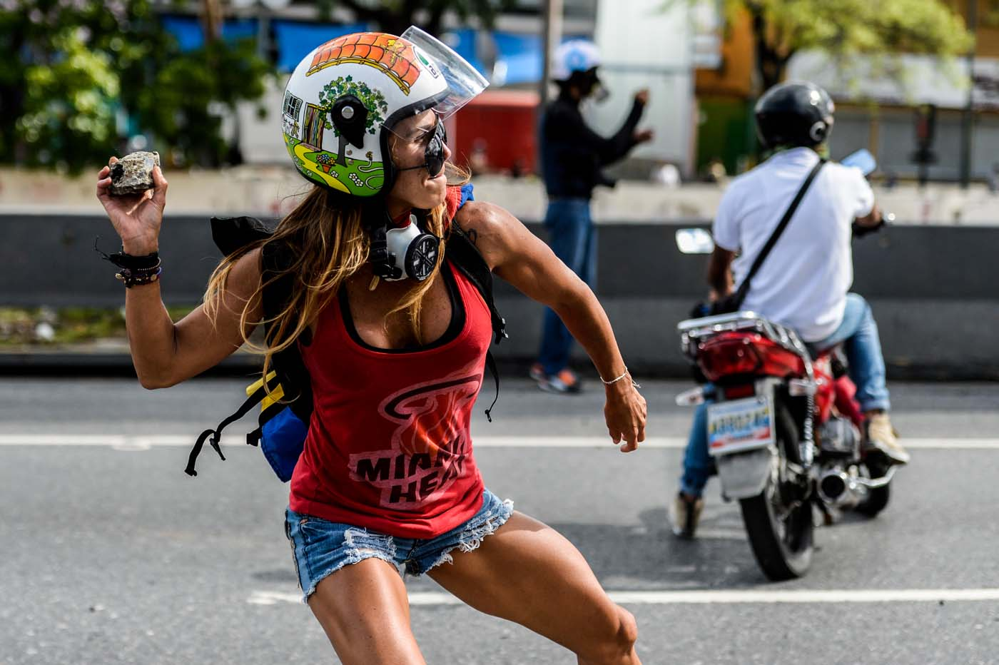"(FILES) This file photo taken on May 01, 2017 shows an opposition activist throwing a stone during a march against Venezuelan President Nicolas Maduro held on May Day, in Caracas on May 1, 2017. ""That is me all over, the strength and the passion,"" Ciarcelluti, 44, told AFP. ""I never run out of energy.""  She says she hopes to be ""an inspiration"" to other protesters. ""We are getting there,"" she says.  / AFP PHOTO / FEDERICO PARRA"