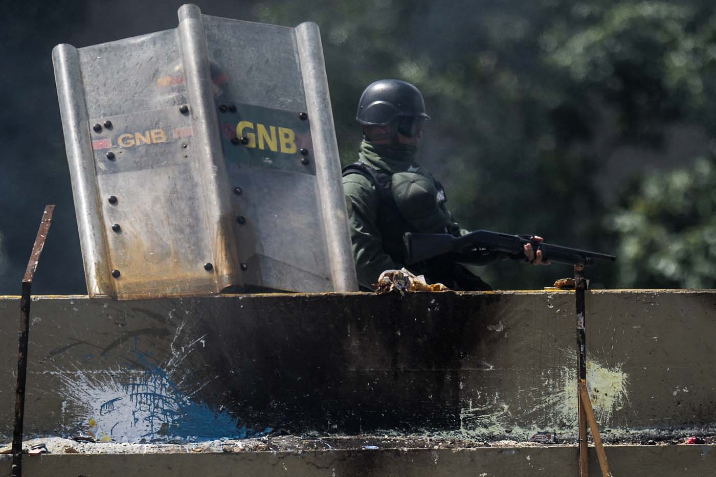 Riot police officers confront opposition activists during a demonstration against Venezuelan President Nicolas Maduro in Caracas, on May 26, 2017. Riot police in Venezuela fired tear gas and water cannon to stop anti-government protesters from marching on a key military installation Friday during the latest violence in nearly two months of unrest. / AFP PHOTO / Federico PARRA
