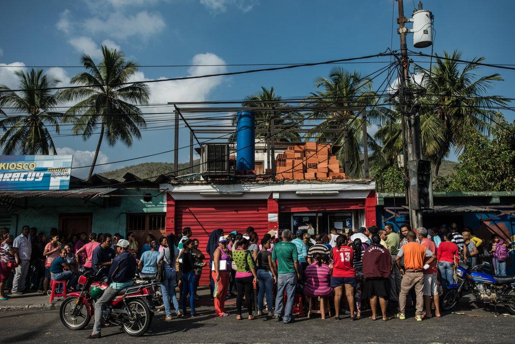 Una fila de cientos de personas que esperaban poder comprar alimentos en un supermercado estatal de la ciudad portuaria de Puerto Cabello. Credit Meridith Kohut para The New York Times