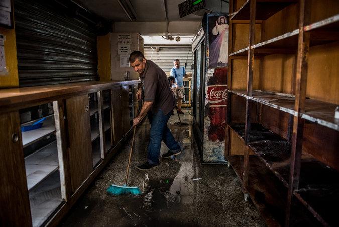 Los trabajadores de un supermercado de Caracas limpian el local después de un saqueo, en abril. Credit Meridith Kohut para The New York Times