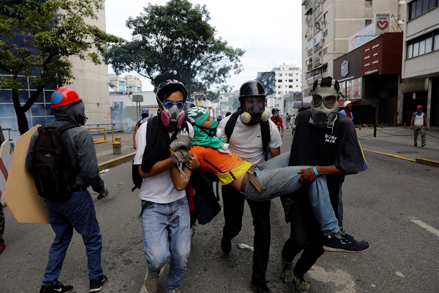 An injured opposition supporter is helped by others during a rally against President Nicolas Maduro in Caracas, Venezuela, May 3, 2017. REUTERS/Carlos Garcia Rawlins