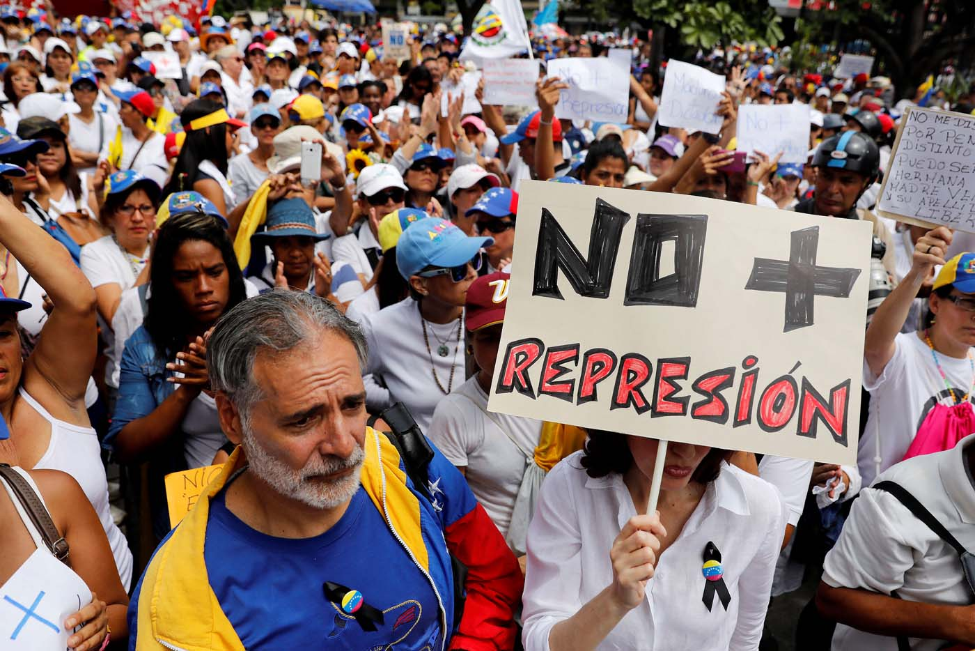 "A woman holds up a placard that reads ""No more repression"" during a women's march to protest against President Nicolas Maduro's government in Caracas, Venezuela May 6, 2017. REUTERS/Carlos Garcia Rawlins"