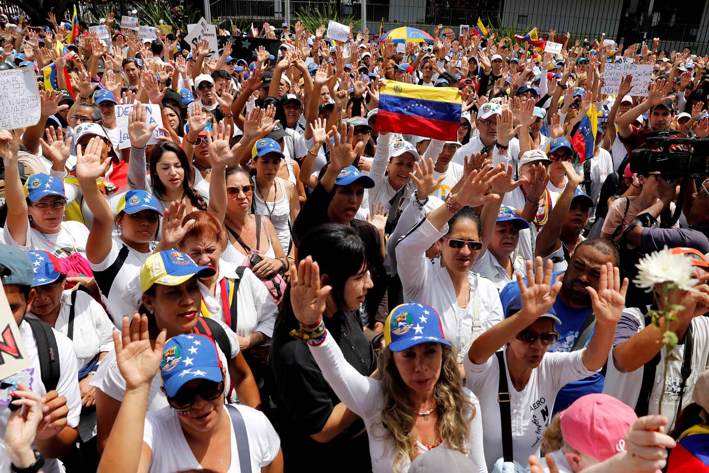 Women lift their hands as they attend a women's march to protest against President Nicolas Maduro's government in Caracas, Venezuela May 6, 2017. REUTERS/Carlos Garcia Rawlins