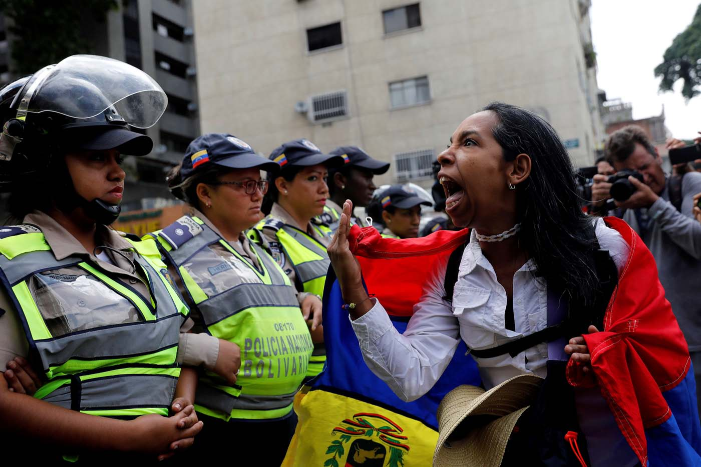 A demonstrator shouts slogans in front of police officers during a women's march to protest against President Nicolas Maduro's government in Caracas, Venezuela May 6, 2017. REUTERS/Carlos Garcia Rawlins