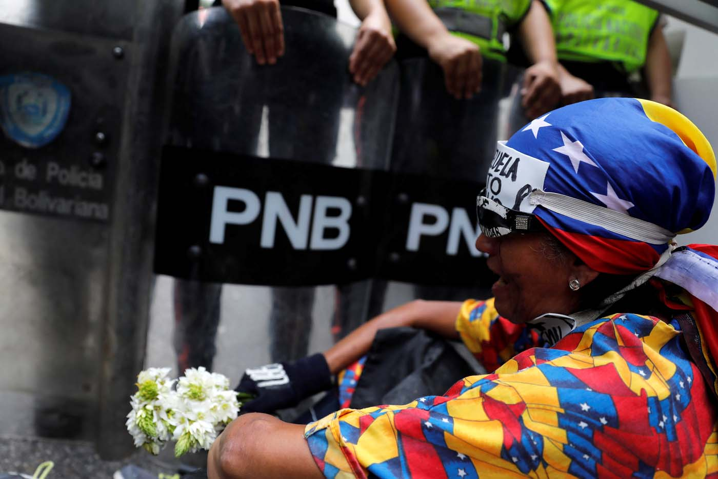 A demonstrator holds flowers next to riot policemen during a women's march to protest against President Nicolas Maduro's government in Caracas, Venezuela, May 6, 2017. REUTERS/Carlos Garcia Rawlins