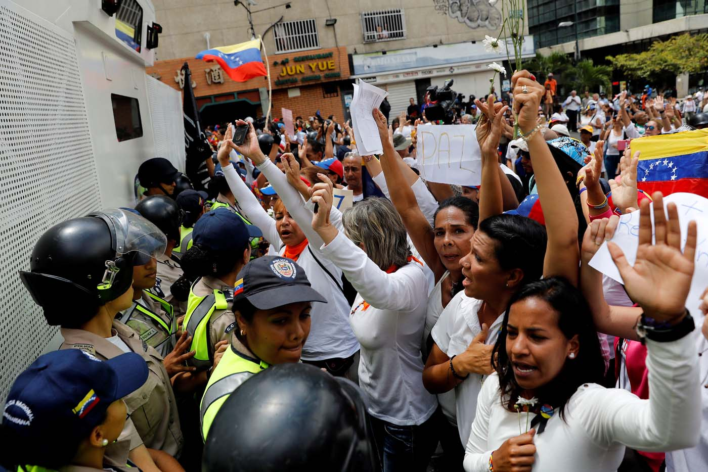 Women lift their hands in front of the police during a women's march to protest against President Nicolas Maduro's government in Caracas, Venezuela May 6, 2017. REUTERS/Carlos Garcia Rawlins