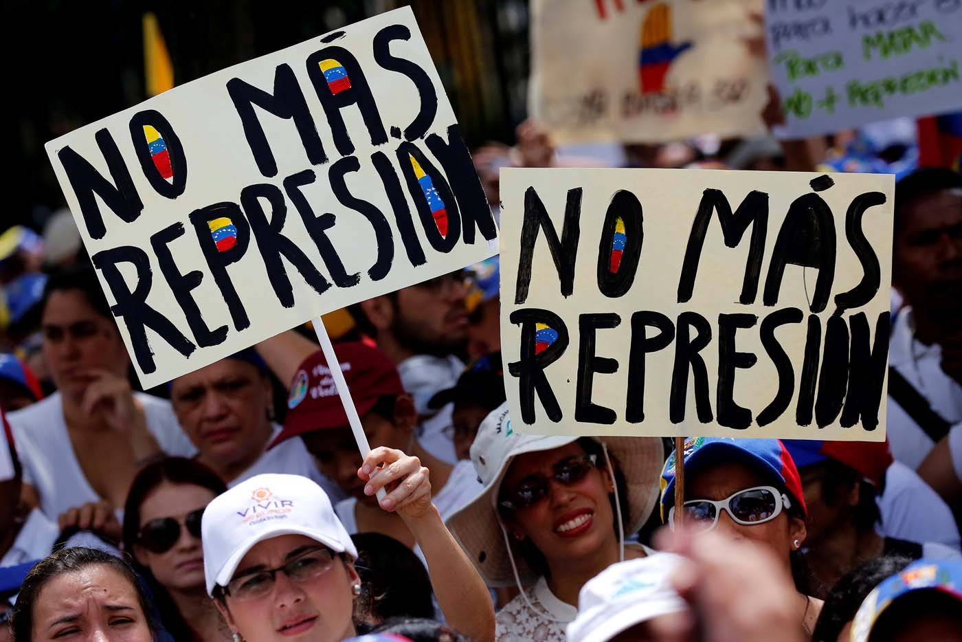 "Demonstrators hold placards that read ""No more repression"" during a women's march to protest against President Nicolas Maduro's government in Caracas, Venezuela, May 6, 2017. REUTERS/Carlos Garcia Rawlins"