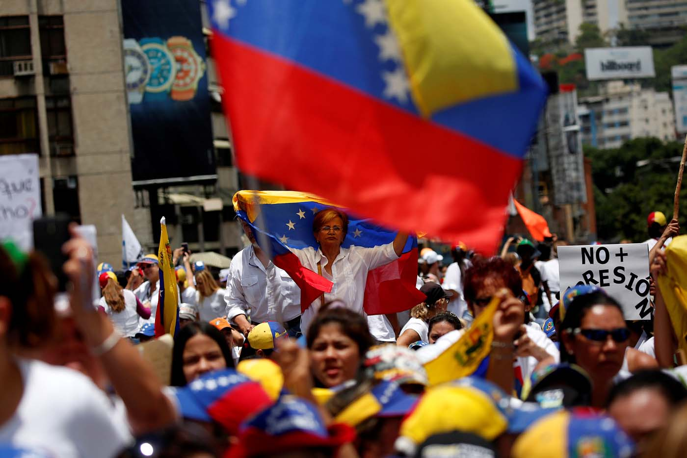 Demonstrators hold Venezuelan flags as they attend a women's march to protest against President Nicolas Maduro's government in Caracas, Venezuela, May 6, 2017. REUTERS/Carlos Garcia Rawlins