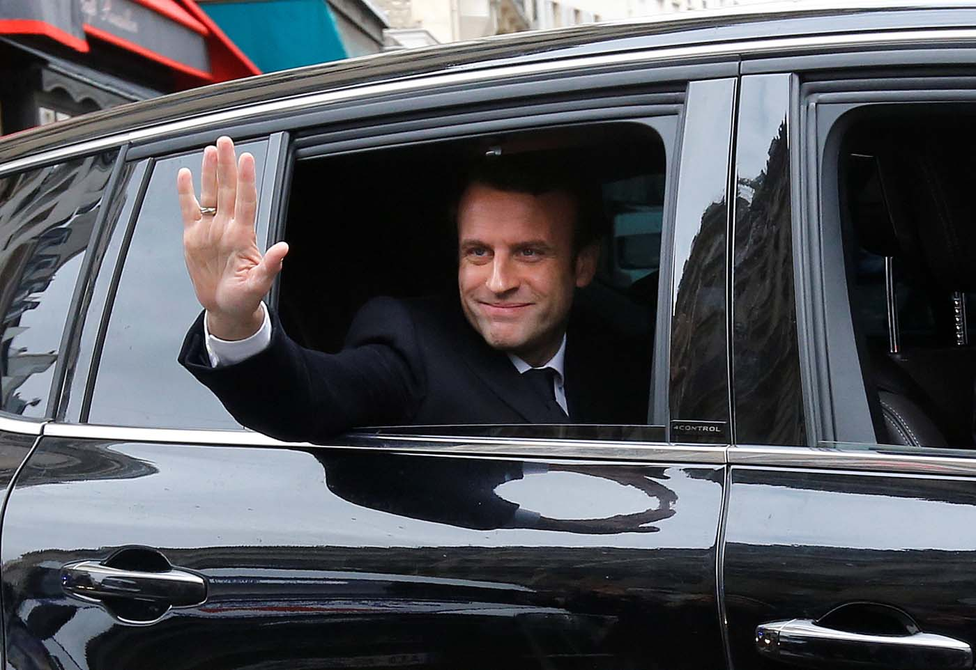 Emmanuel Macron, head of the political movement En Marche !, or Onwards !, and candidate for the 2017 presidential election, waves from his car as he leaves his home during the second round of the election, in Paris, France, May 7, 2017. REUTERS/Jean-Paul Pelissier TPX IMAGES OF THE DAY