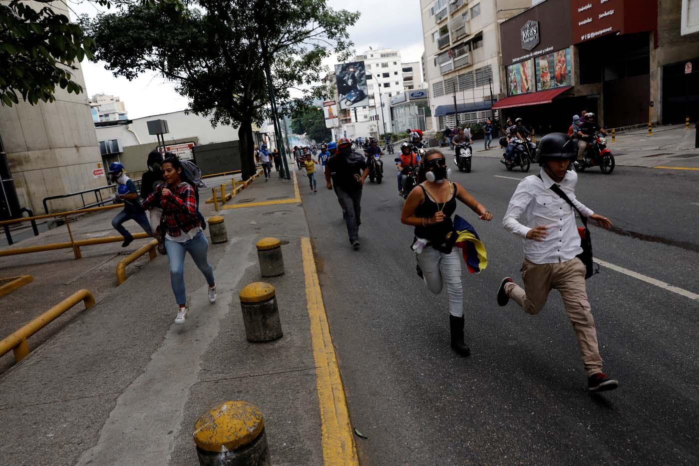 Opposition supporters run away while rallying against Venezuelan President Nicolas Maduro in Caracas, Venezuela, May 8, 2017. REUTERS/Carlos Garcia Rawlins