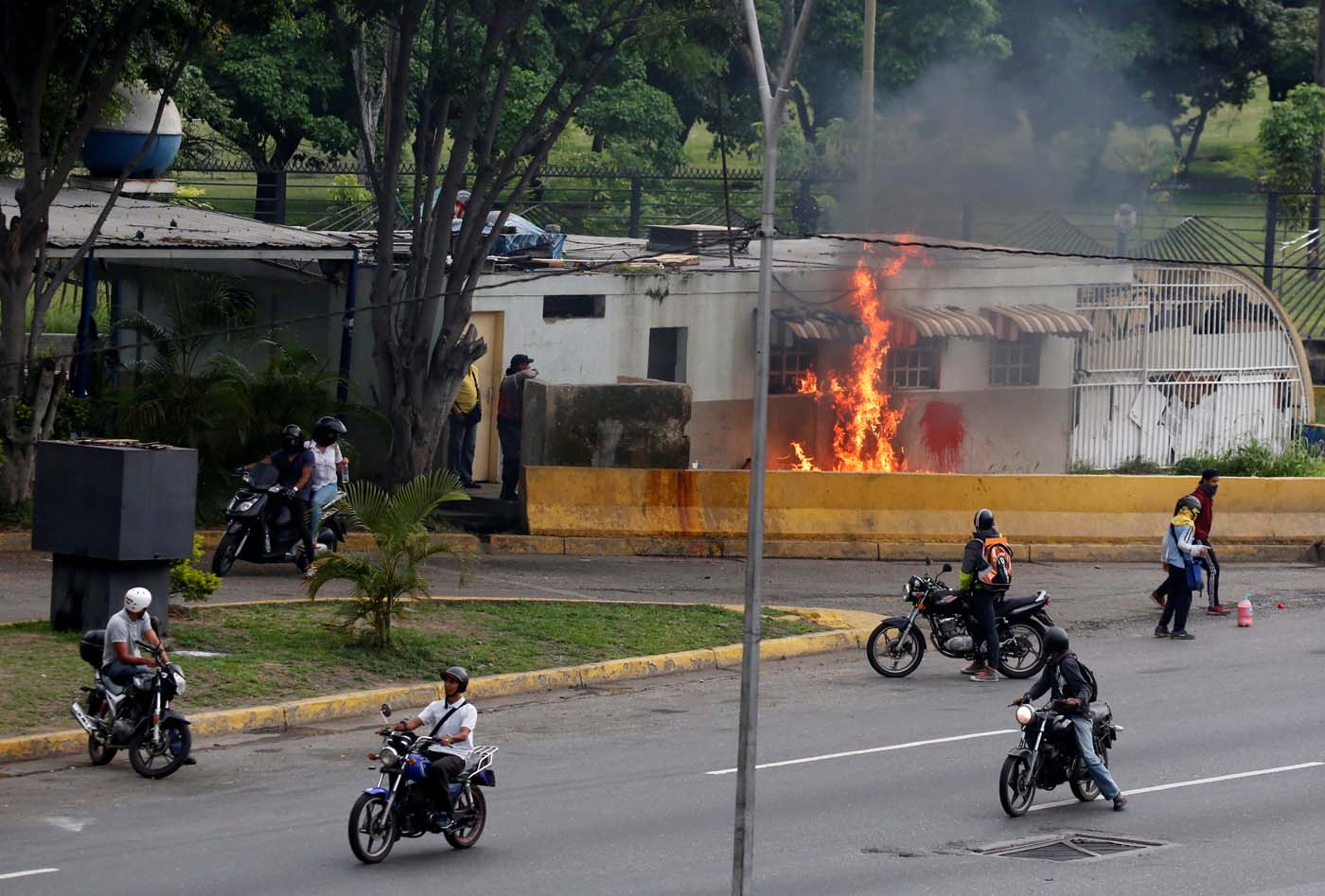 Opposition supporters set a building on fire while clashing with riot police during a rally against Venezuelan President Nicolas Maduro in Caracas, Venezuela, May 8, 2017. REUTERS/Carlos Garcia Rawlins
