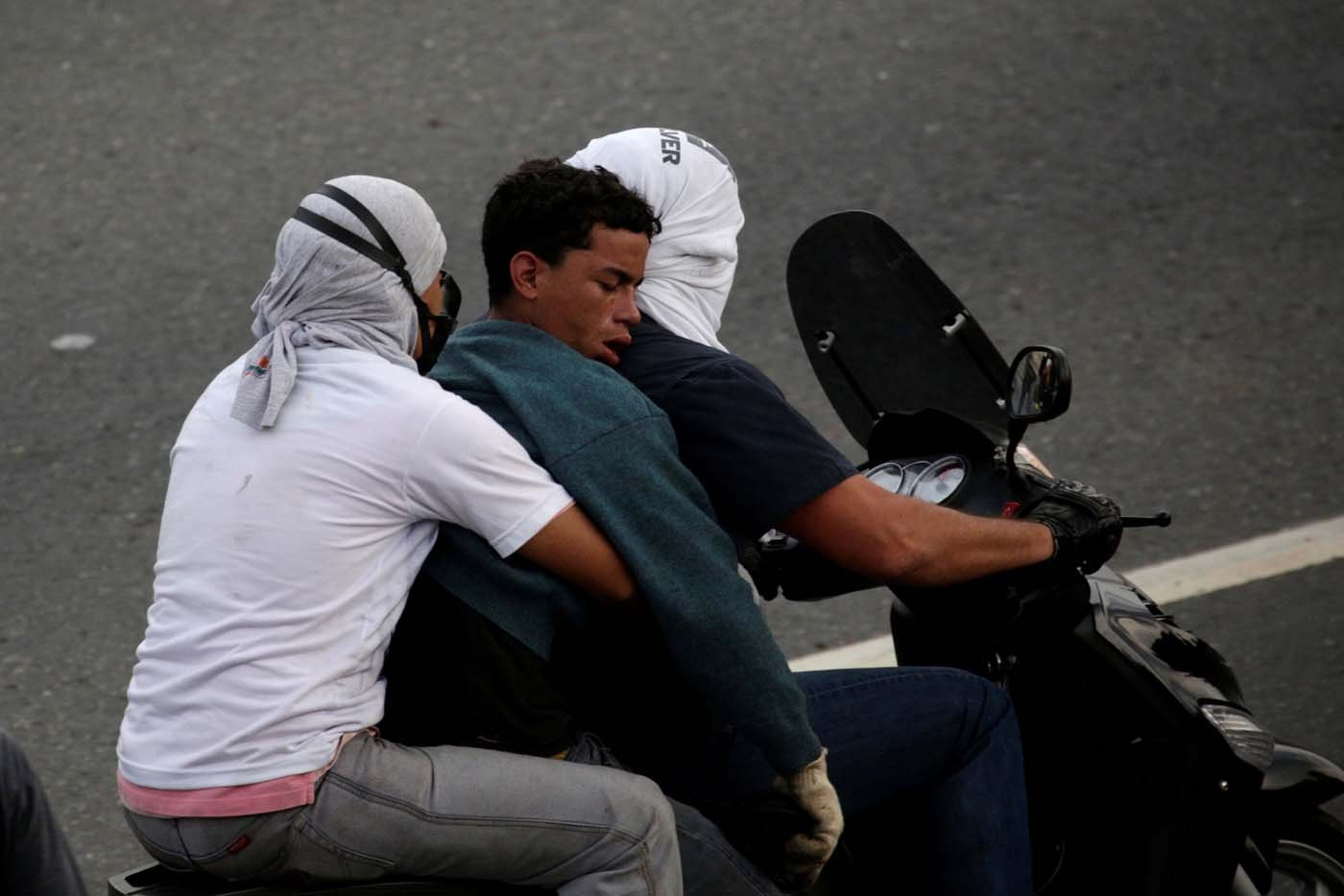 An injured opposition supporter is helped by others during a rally against President Nicolas Maduro in Caracas, Venezuela, May 8, 2017. REUTERS/Marco Bello