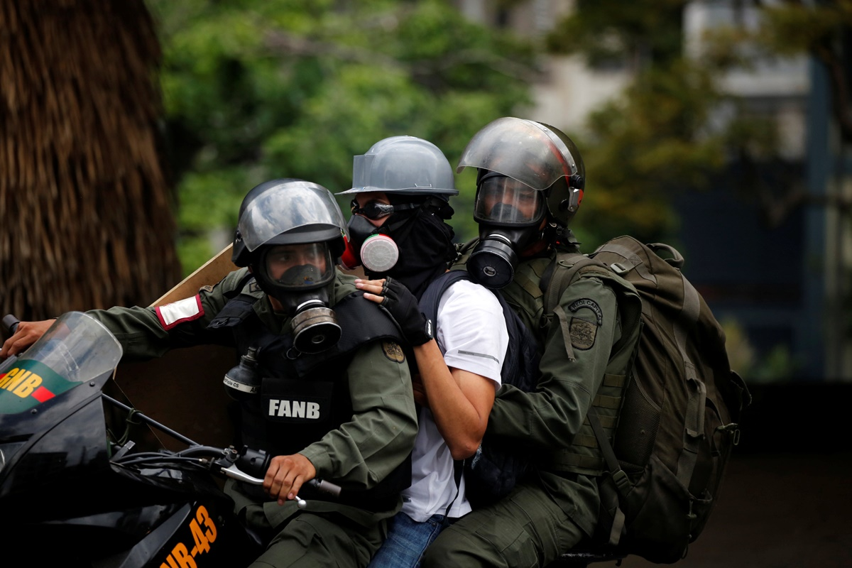 A demonstrator is detained by riot security forces during a protest against Venezuela's President Nicolas Maduro's government in Caracas, Venezuela, May 13, 2017. REUTERS/Carlos Garcia Rawlins