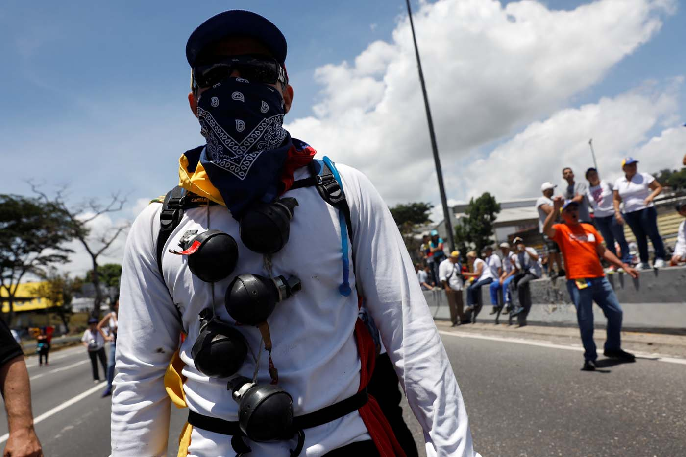 An opposition supporter rallies against President Nicolas Maduro with used tear gas grenades tied around his neck in Caracas, Venezuela, May 20, 2017. REUTERS/Carlos Garcia Rawlins