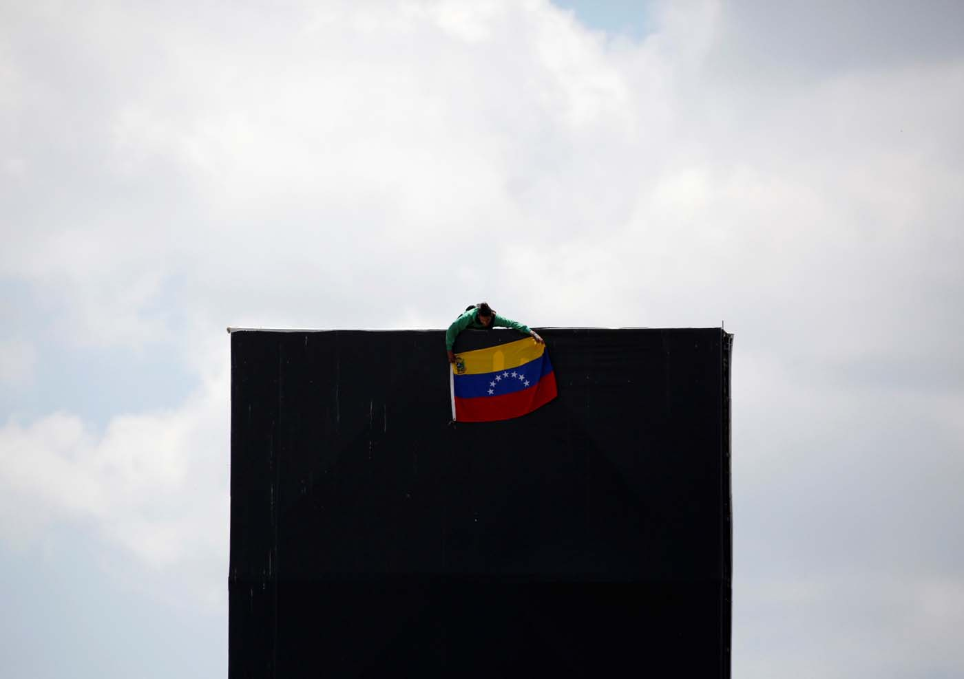 An opposition supporter hang a national flag on top of an advertising structure while rallying against President Nicolas Maduro in Caracas, Venezuela, May 20, 2017. REUTERS/Carlos Garcia Rawlins