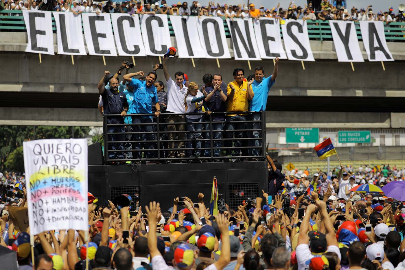 "Venezuelan opposition leader and Governor of Miranda state Henrique Capriles (3L) and Lilian Tintori (4R), wife of jailed opposition leader Leopoldo Lopez, participate in a rally against President Nicolas Maduro in front of a banner that reads ""Elections now"" in Caracas, Venezuela, May 20, 2017. REUTERS/Carlos Barria"