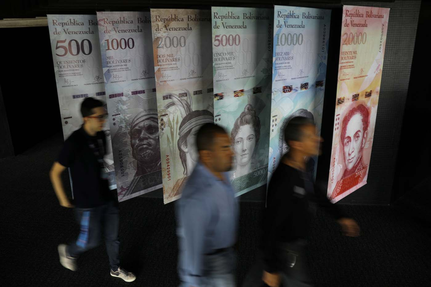People walk by banners of Venezuelan bolivar notes displayed at the Venezuelan Central Bank building in Caracas, Venezuela May 23, 2017. REUTERS/Carlos Barria
