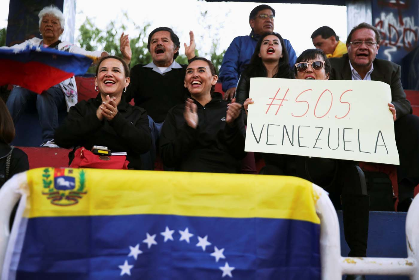 People holding a sign reads; ' SOS Venezuela' attend a protest against a visit by Venezuela's President Nicolas Maduro to Ecuador to attend President Lenin Moreno's inauguration, in Quito, Ecuador, May 23, 2017. REUTERS/Mariana Bazo