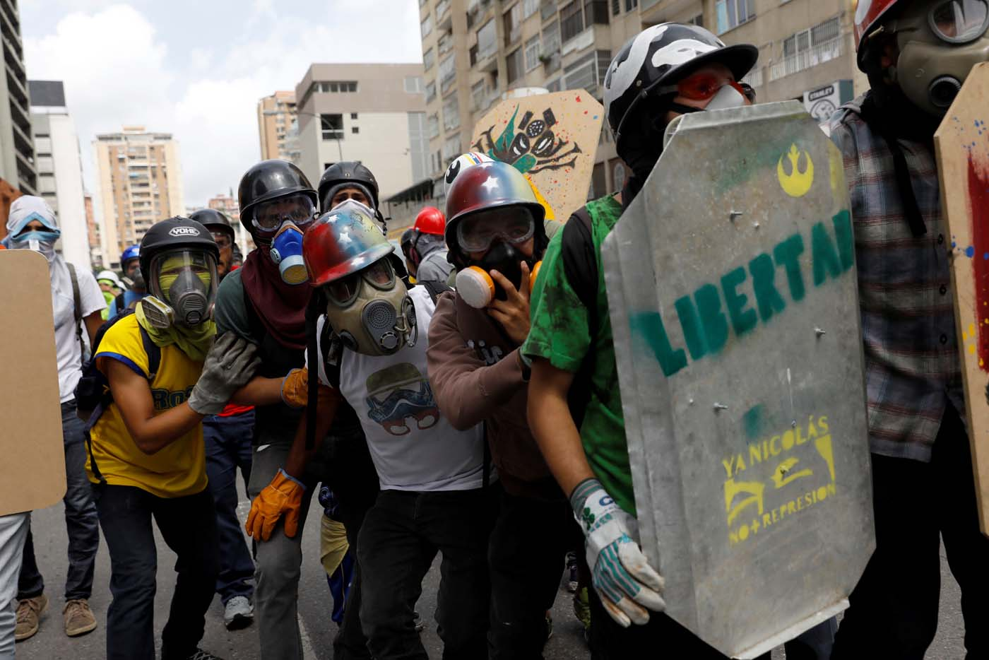 "Demonstrators take cover behind a home-made shield with the word ""freedom"" on it while clashing with riot security forces during a rally against President Nicolas Maduro in Caracas, Venezuela May 24, 2017. REUTERS/Carlos Garcia Rawlins"