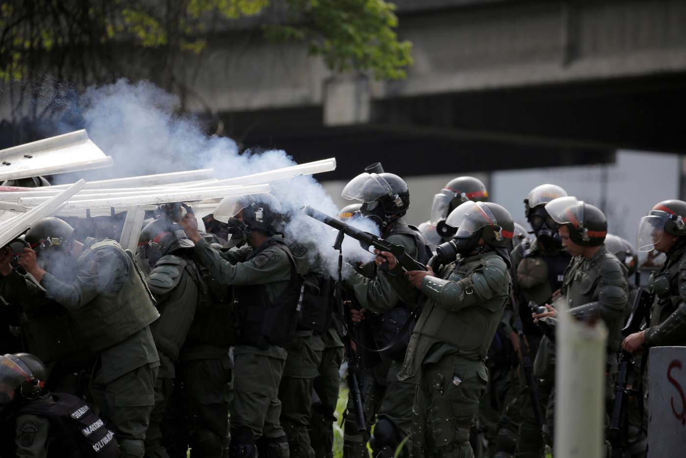Riot security forces take cover while clashing with demonstrators rallying against President Nicolas Maduro in Caracas, Venezuela, May 24, 2017. REUTERS/Carlos Barria