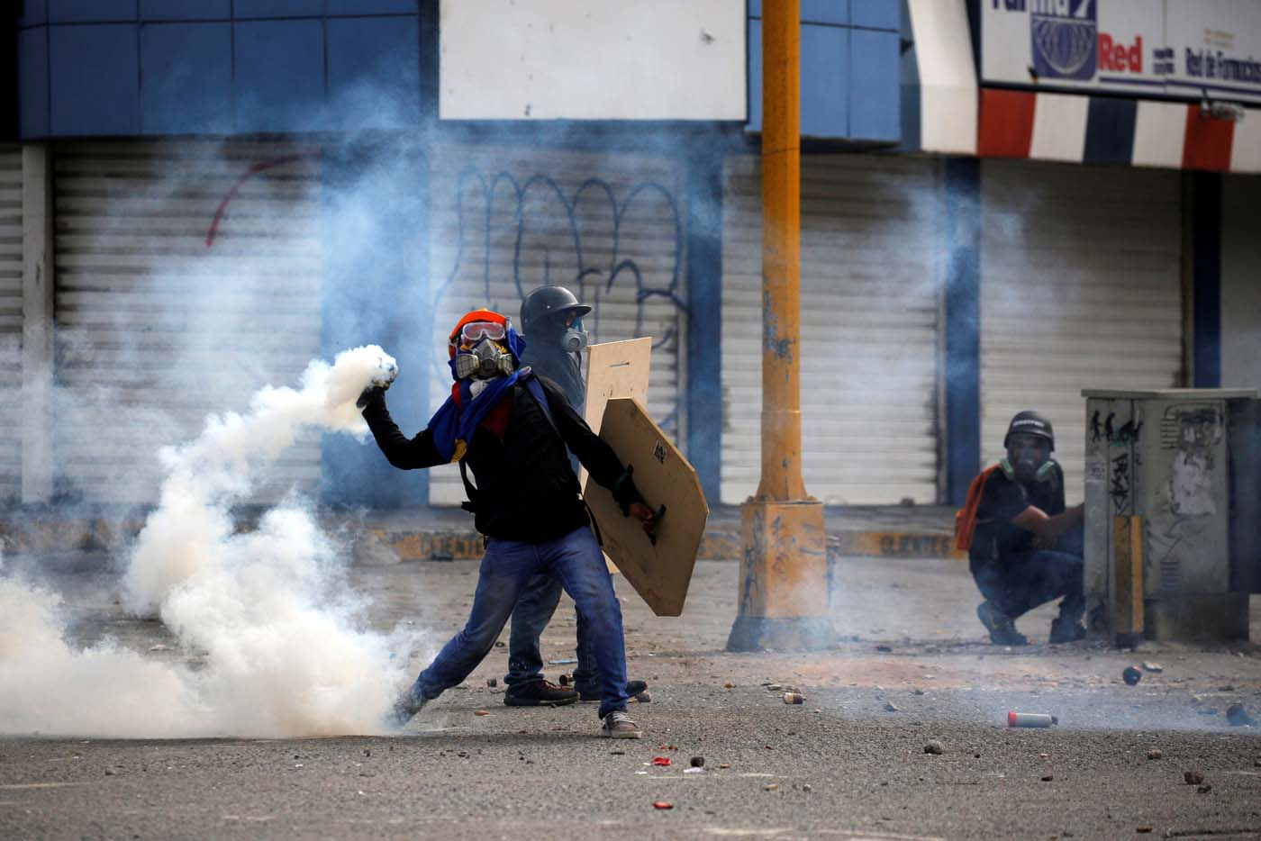 A demonstrator throws back a tear gas canister while clashing with riot security forces during a rally against President Nicolas Maduro in Caracas, Venezuela, May 24, 2017. REUTERS/Carlos Barria