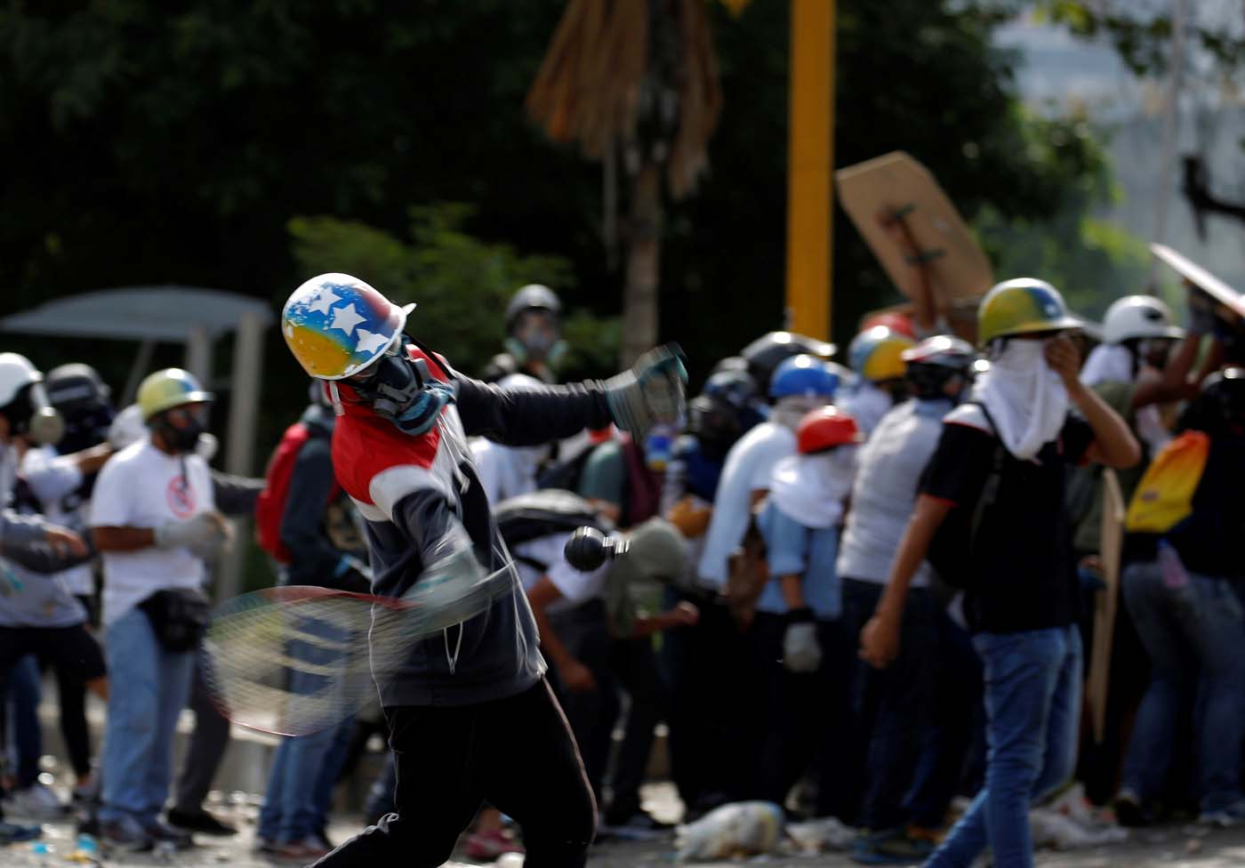 A demonstrator uses a racket to hit a tear gas canister while clashing with riot security forces during a rally against President Nicolas Maduro in Caracas, Venezuela, May 24, 2017. REUTERS/Carlos Barria
