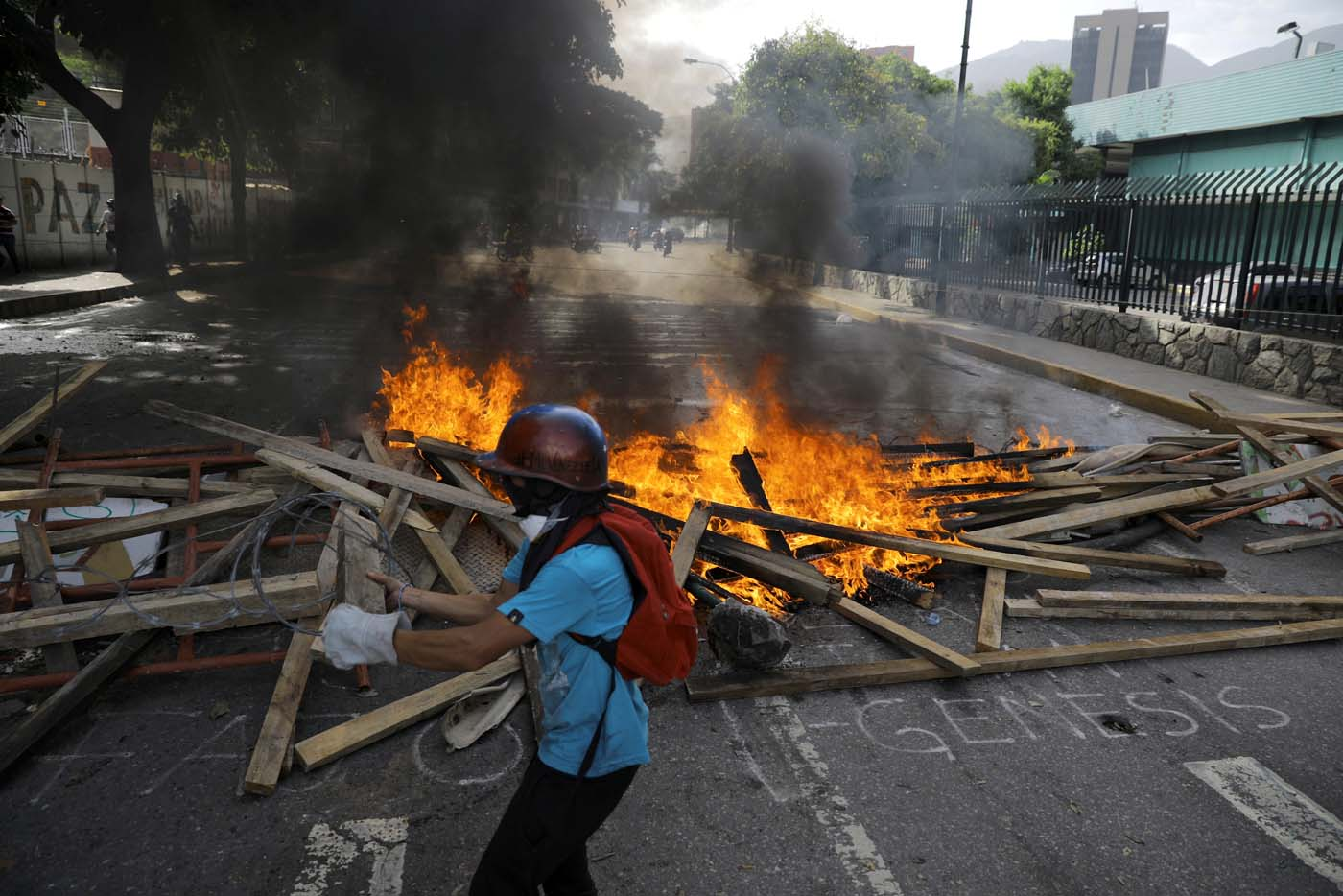 A demonstrator walks in front of a fire barricade while clashing with riot security forces during a rally against President Nicolas Maduro in Caracas, Venezuela, May 24, 2017. REUTERS/Carlos Barria