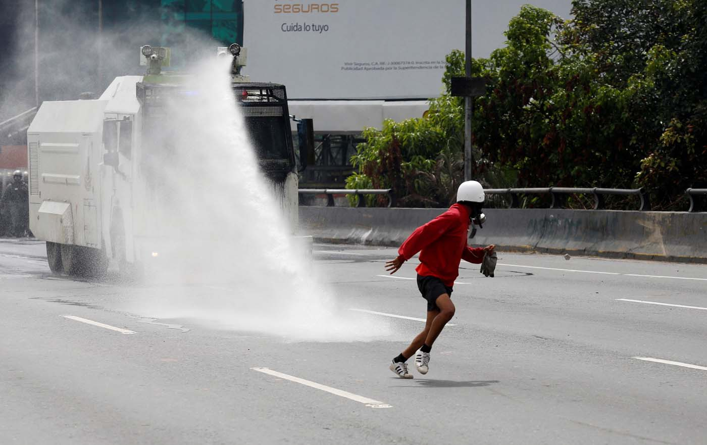 A demonstrator runs away from a water canon while clashing with riot security forces during a rally against President Nicolas Maduro in Caracas, Venezuela, May 24, 2017. REUTERS/Marco Bello