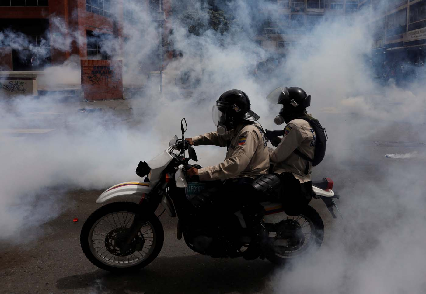 Riot security forces ride a dirt bike while clashing with demonstrators rallying against President Nicolas Maduro in Caracas, Venezuela, May 24, 2017. REUTERS/Carlos Garcia Rawlins