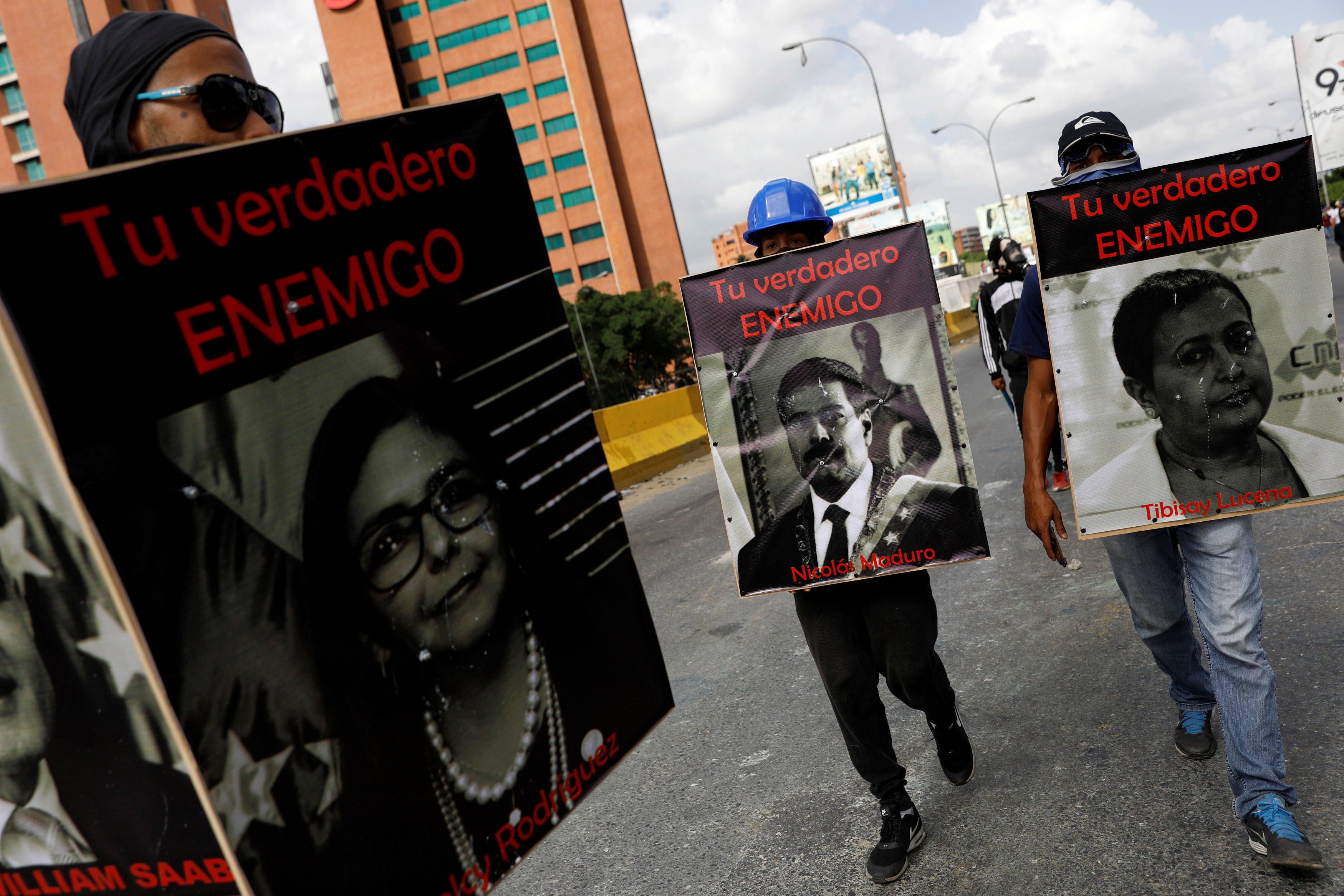 "Demonstrators carry signs with images of President Nicolas Maduro (C), National Electoral Council (CNE) President Tibisay Lucena and Minister of Foreign affairs Delcy Rodriguez (L) that reads ""your real enemy"" while rallying against President Nicolas Maduro in Caracas, Venezuela, May 27, 2017. REUTERS/Carlos Garcia Rawlins"