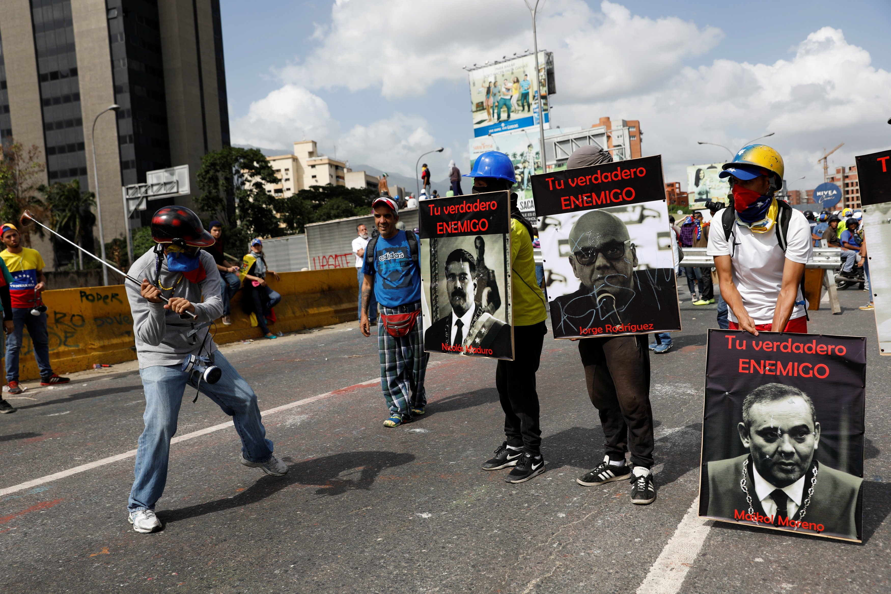 "Demonstrators carry signs with images of President Nicolas Maduro (L) and politician Jorge Rodriguez and judge Maikol Moreno (R) that reads ""your real enemy"" while rallying against President Nicolas Maduro in Caracas, Venezuela, May 27, 2017. REUTERS/Carlos Garcia Rawlins"