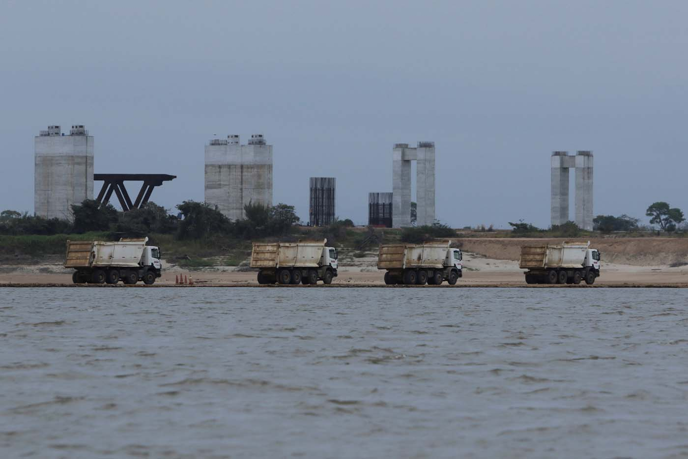 Trucks are seen at a construction site by Odebrecht of the third bridge over the Orinoco River in Caicara del Orinoco, Venezuela March 21, 2017. Picture taken March 21, 2017. REUTERS/William Urdaneta