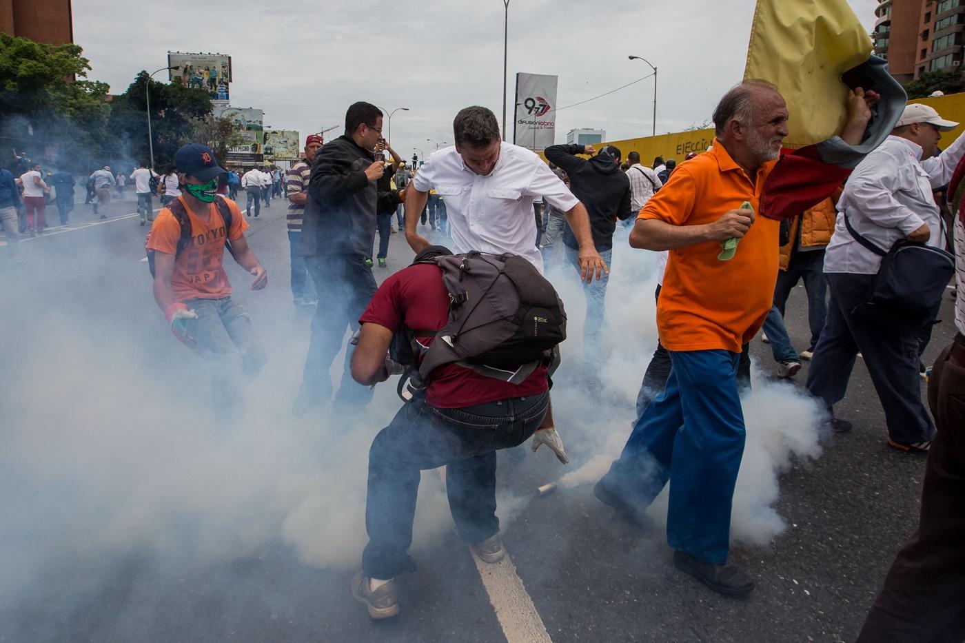 CAR007. CARACAS (VENEZUELA), 03/05/2017 - Un grupo de diputados de la Asamblea Nacional reacciona ante una bomba de gas lacrimógeno lanzada por la policía durante una mnaifestación que encabezan hoy, miércoles 3 de mayo de 2017, en Caracas (Venezuela). La Guardia Nacional Bolivariana (GNB, policía militarizada) de Venezuela dispersó hoy con gases lacrimógenos una movilización opositora en el este de Caracas que pretendía llegar hasta la sede de la Asamblea Nacional (AN, Parlamento), ubicada en el centro de la capital. EFE/MIGUEL GUTIERREZ