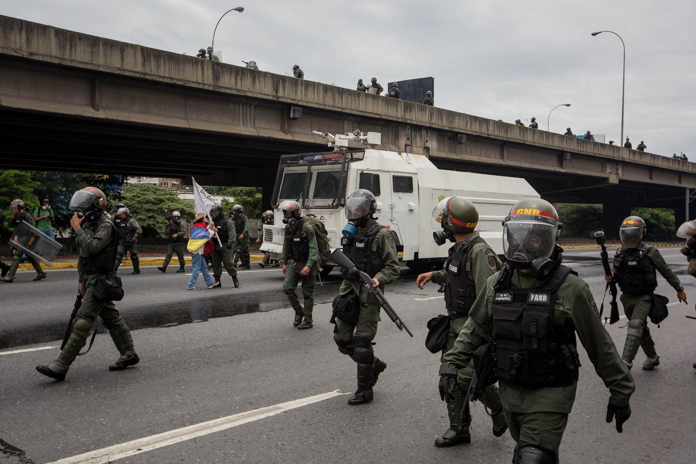 CAR010. CARACAS (VENEZUELA), 03/05/2017 - Militares intentan retirar a una mujer que bloquea el paso de una tanqueta de la Guardia Nacional durante una manifestación encabezada por diputados opositores hoy, miércoles 3 de mayo de 2017, en Caracas (Venezuela). La Guardia Nacional Bolivariana (GNB, policía militarizada) de Venezuela dispersó hoy con gases lacrimógenos una movilización opositora en el este de Caracas que pretendía llegar hasta la sede de la Asamblea Nacional (AN, Parlamento), ubicada en el centro de la capital. EFE/MIGUEL GUTIERREZ
