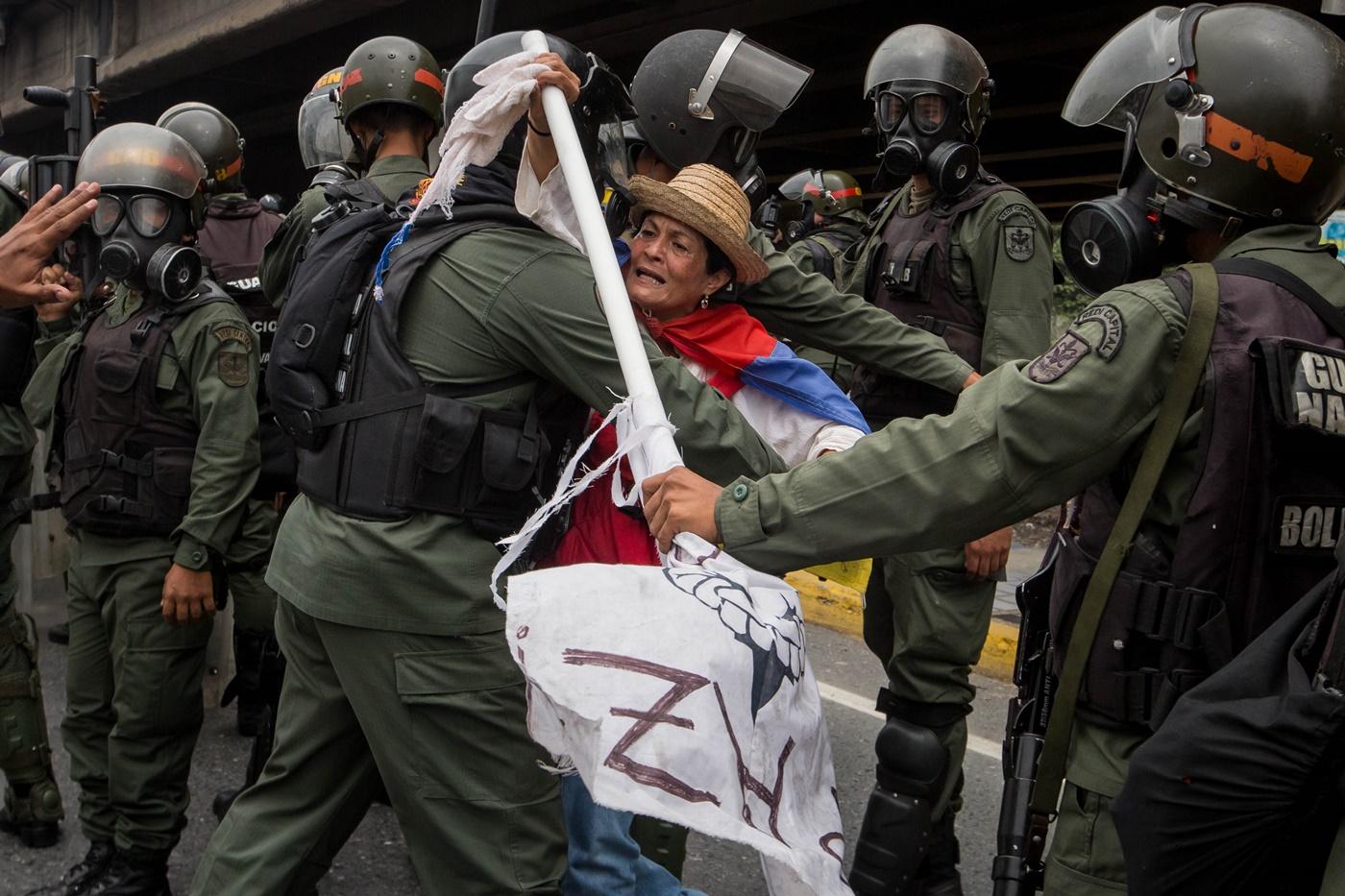CAR013. CARACAS (VENEZUELA), 03/05/2017 - Militares retiran a una mujer que bloqueaba el paso de una tanqueta de la Guardia Nacional durante una manifestación encabezada por diputados opositores hoy, miércoles 3 de mayo de 2017, en Caracas (Venezuela). La Guardia Nacional Bolivariana (GNB, policía militarizada) de Venezuela dispersó hoy con gases lacrimógenos una movilización opositora en el este de Caracas que pretendía llegar hasta la sede de la Asamblea Nacional (AN, Parlamento), ubicada en el centro de la capital. EFE/MIGUEL GUTIERREZ