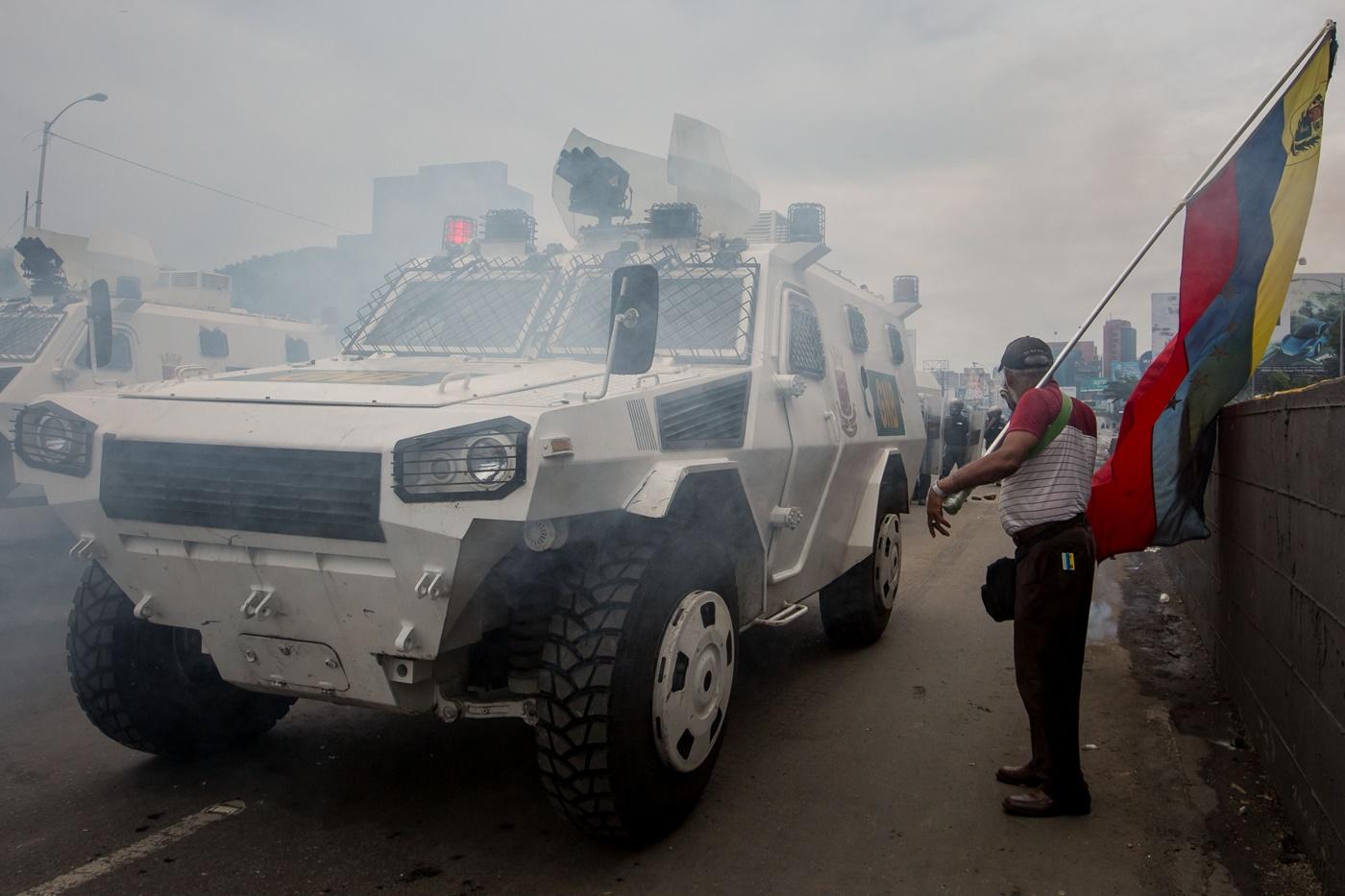 CAR019. CARACAS (VENEZUELA), 03/05/2017 - Un hombre con una bandera venezolana permanece junto a unas tanquetas de la Guardia Bolivariana durante una manifestación hoy, miércoles 3 de mayo de 2017, en Caracas (Venezuela). La Guardia Nacional Bolivariana (GNB, policía militarizada) de Venezuela dispersó hoy con gases lacrimógenos una movilización opositora en el este de Caracas que pretendía llegar hasta la sede de la Asamblea Nacional (AN, Parlamento), ubicada en el centro de la capital. EFE/MIGUEL GUTIERREZ