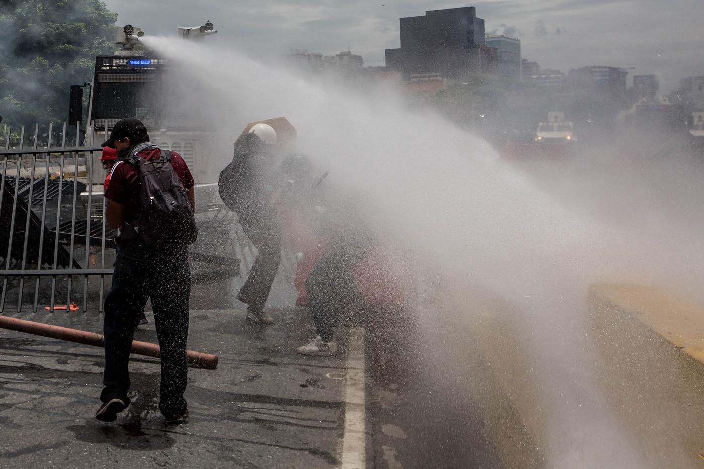 CAR023. CARACAS (VENEZUELA), 03/05/2017 - Miembros de la Guardia Bolivariana lanzan un chorro de agua a presión a un grupo de manifestantes hoy, miércoles 3 de mayo de 2017, en Caracas (Venezuela). La Guardia Nacional Bolivariana (GNB, policía militarizada) de Venezuela dispersó hoy con gases lacrimógenos una movilización opositora en el este de Caracas que pretendía llegar hasta la sede de la Asamblea Nacional (AN, Parlamento), ubicada en el centro de la capital. EFE/MIGUEL GUTIERREZ