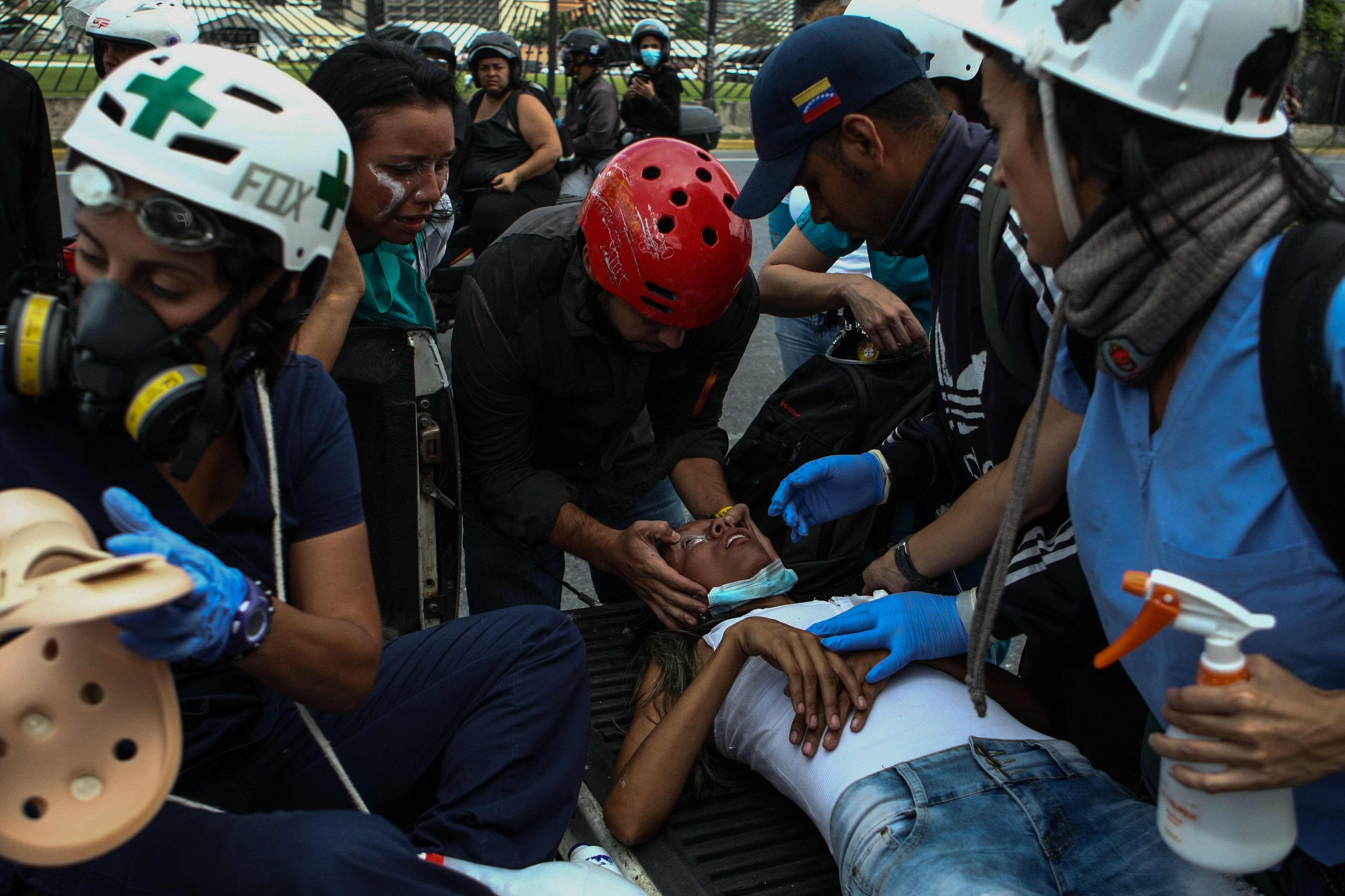 VEN053. CARACAS (VENEZUELA), 24/05/2017-. Una manifestante desmayada por los gases lacrimógenos es auxiliada por rescatistas hoy, miércoles 24 de mayo de 2017, durante una protesta contra el Gobierno en Caracas (Venezuela). Una manifestación convocada por la oposición venezolana en Caracas terminó hoy con 62 lesionados, entre ellos un diputado opositor y tres heridos por arma de fuego, informó el director de salud del municipio caraqueño Baruta, Enrique Montbrun. EFE/CRISTIAN HERNANDEZ
