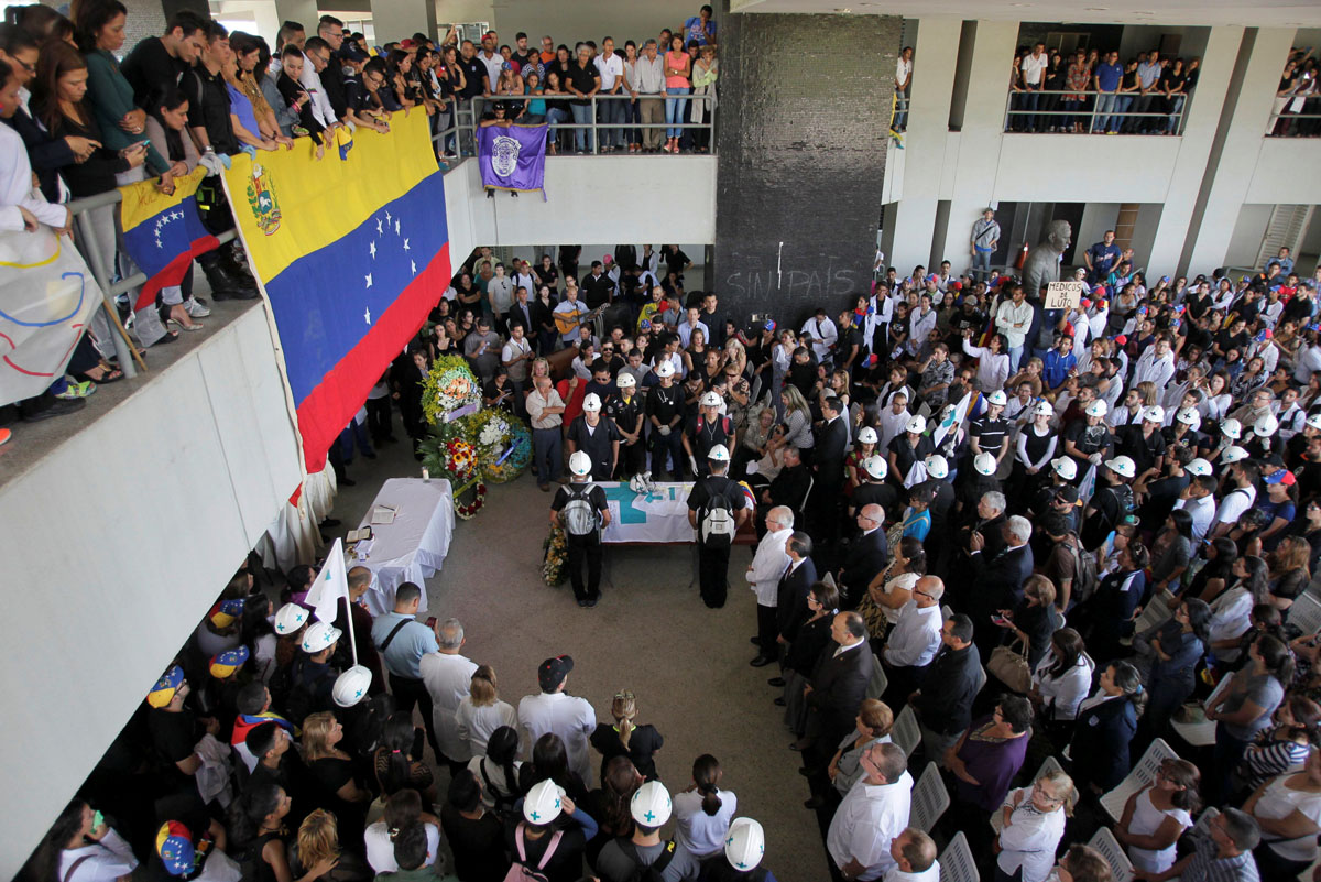 Volunteers, members of a primary care response team and mourners,attend the funeral of their fellow team mate Paul Moreno, who died while on duty during a protest a ainst Venezuelan President Nicolas Maduro's government in Maracaibo, Venezuela, May 19, 2017. REUTERS/Isaac Urrutia