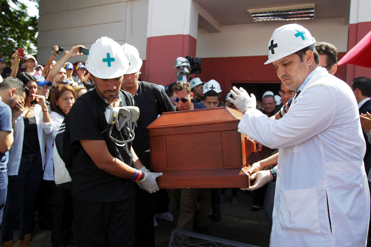 Volunteers, members of a primary care response team and mourners carry the coffin of their fellow team mate Paul Moreno, who died while on duty during a protest against Venezuelan President Nicolas Maduro's government in Maracaibo, Venezuela, May 19, 2017. REUTERS/Isaac Urrutia