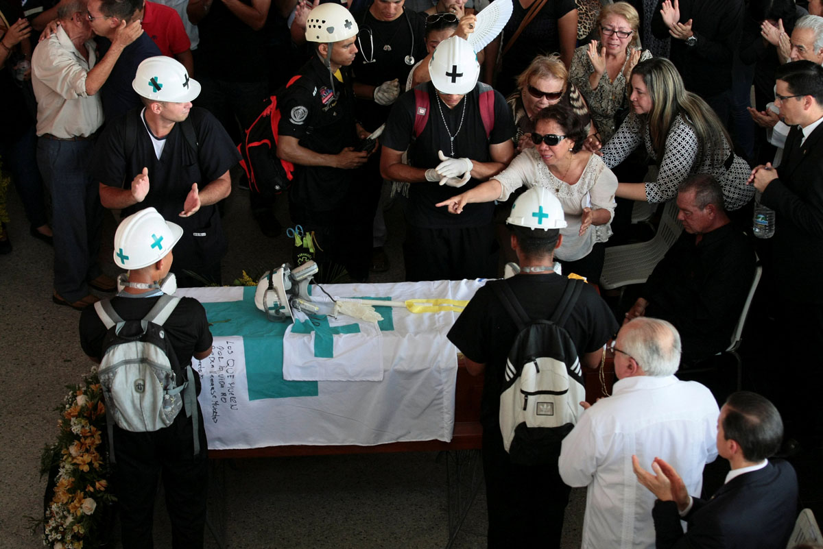 Volunteers, members of a primary care response team and mourners stand next to the coffin of their fellow team mate Paul Moreno, who died while on duty during a protest against Venezuelan President Nicolas Maduro's government in Maracaibo, Venezuela, May 19, 2017. REUTERS/Isaac Urrutia