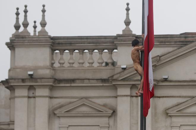 CHI02. SANTIAGO (CHILE), 25/05/2017.- Un hombre desnudo trepa el mástil de la bandera chilena en frente del Palacio de La Moneda hoy, jueves 25 de mayo de 2017, en Santiago (Chile). En una inusual protesta, de la que se desconocen hasta el momento los motivos, el hombre permaneció varios minutos en el mástil hasta que se lanzó y cayó sobre un autobús de los carabineros de la policía chilena, quienes aseguraron que el sujeto tiene problemas mentales. EFE/Marcelo Rodríguez
