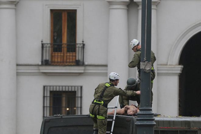 CHI03. SANTIAGO (CHILE), 25/05/2017.- Un hombre desnudo es detenido por la policía chilena luego de que este se lanzara sobre el vehículo policiaco tras trepar el mástil de la bandera chilena en frente del Palacio de La Moneda hoy, jueves 25 de mayo de 2017, en Santiago (Chile). En una inusual protesta, de la que se desconocen hasta el momento los motivos, el hombre permaneció varios minutos en el mástil hasta que se lanzó y cayó sobre un autobús de los carabineros de la policía chilena, quienes aseguraron que el sujeto tiene problemas mentales. EFE/Marcelo Rodríguez